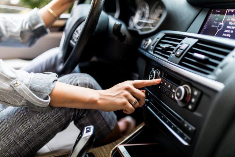 car-dashboard-radio-closeup-woman-sets-up-radio-while-driving-car (1)
